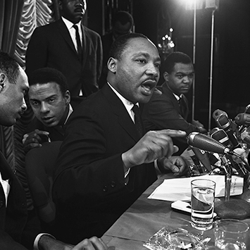 Martin Luther King with Andrew Young and Al Raby at press conference at Sahara Hotel Chicago, IL. King announces the Open City campaign to fight problems of the poor in the North. This is the SCLC's first true Northern campaign. Jan. 7, 1966
